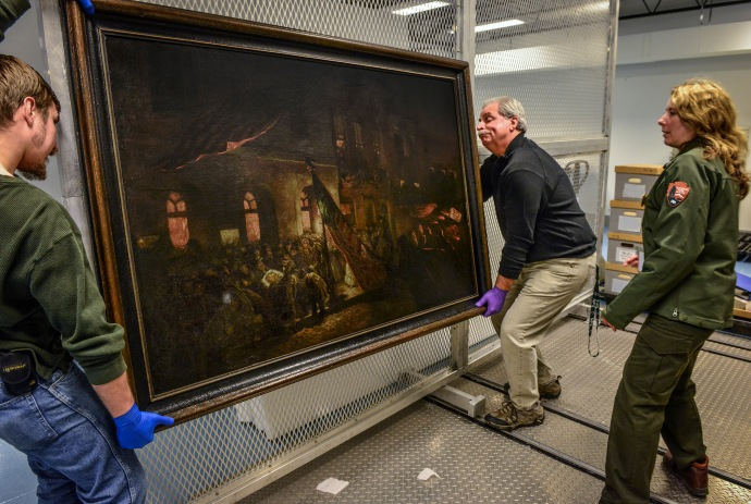 HYATTSVILLE, MD - APRIL 8: The National Park Service museum has a painting by an eyewitness of Lincoln being carried from Ford's Theater after being shot, on April, 08, 2015 in Hyattsville, MD. Pictured, from left, Lyndon Novotny, materials handler, Bob Sonderman, Director & regional curator, and Laura Anderson, National Park Service museum curator for the National Mall. (Photo by Bill O'Leary/The Washington Post)